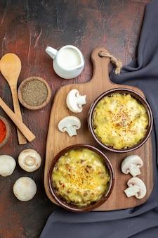 Vista dall'alto gustosa julienne in ciotole sul tagliere cucchiai di legno spezie in piccole ciotole funghi su marrone