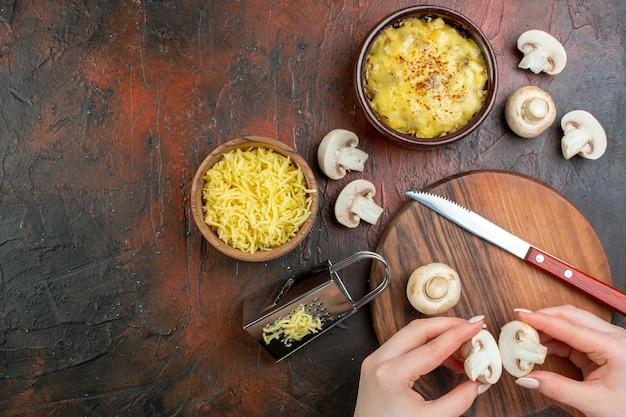 上面図ボウルおろし金でおいしい千切り女性の手でキノコを切るまな板のナイフすりおろしたモサレラボウルの茶色のテーブル