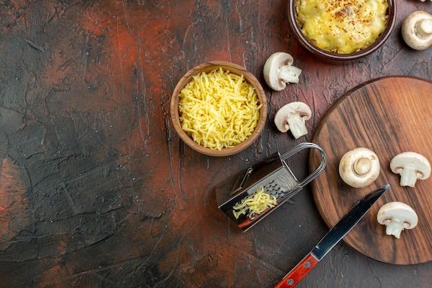 ボウルおろし金のキノコとまな板のナイフの上面図おいしい千切り茶色のテーブルのボウルのすりおろしたモサレラ
