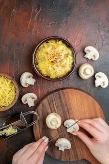 上面図ボウルおろし金の女性の手でおいしい千切りまな板でキノコを切る茶色のテーブルのボウルですりおろしたモサレラ