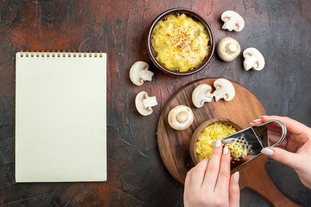 ボウルの生のキノコの女性の手でグレーティングモサレラノートブックの茶色のテーブルにおいしい千切りの上面図