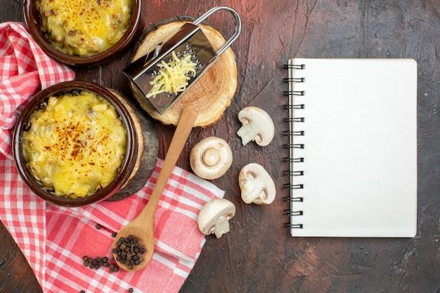 上面図ボウルマッシュルームのおいしいジュリアンミルクボウルノートブックおろし金木の板木のスプーン濃い赤のテーブル