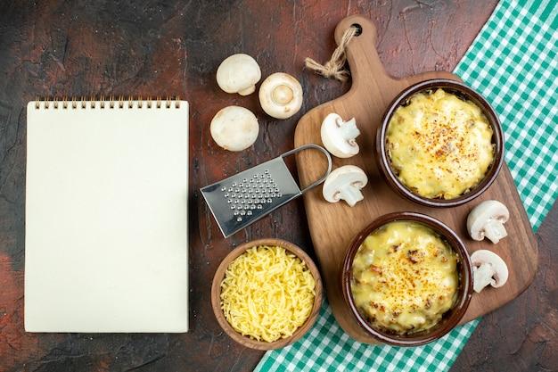 上面図木製のサービングボード上のボウルのおいしい千切りボウルボックスおろし金のモサレラおろし金茶色のテーブルのメモ帳