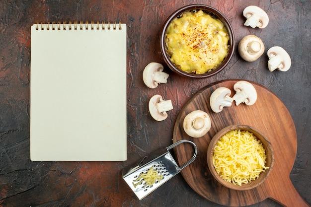 上面図ボウルにおいしい千切り生のキノコミルクボウルおろし金メモ帳茶色のテーブルのまな板のボウルにすりおろしたモサレラ