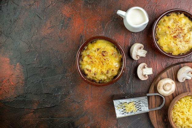 茶色のテーブルにボウル生キノコミルクボウルおろし金でおいしい千切りの上面図