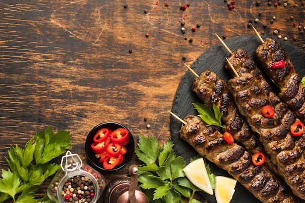 Top view of tasty kebab on plate with herbs and copy space