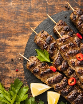 Top view of tasty kebab on slate with herbs
