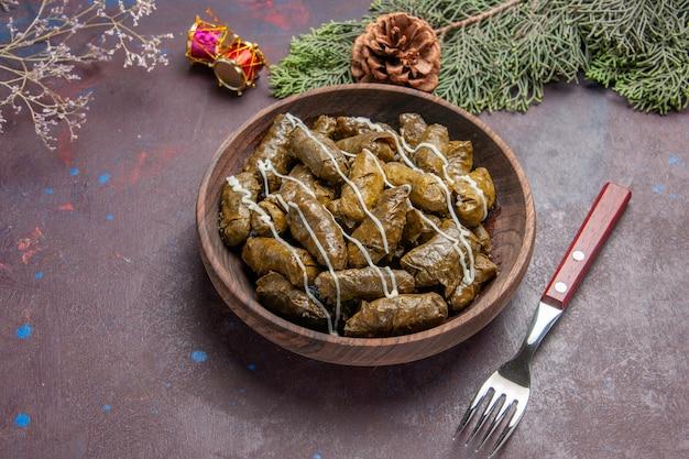 Vista dall'alto gustoso piatto di carne dolma foglia all'interno del piatto marrone su oscurità