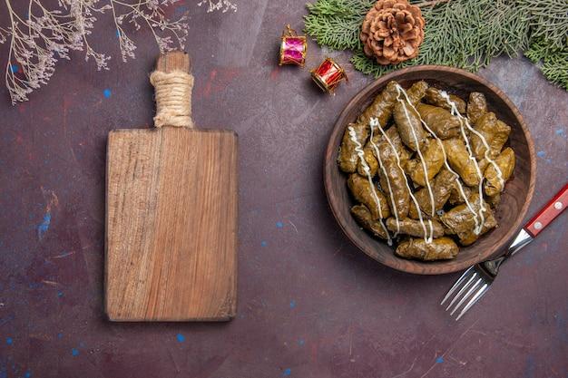 Вид сверху вкусное мясное блюдо из листовой долмы внутри коричневой тарелки на темноте