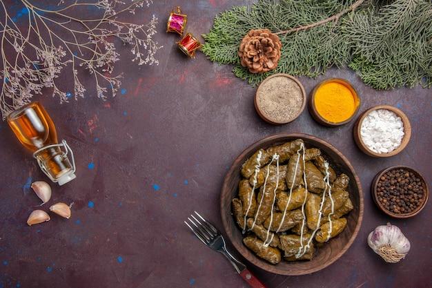 Вид сверху вкусное мясное блюдо из листовой долмы с приправами на темноте