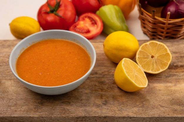 Vista dall'alto di una gustosa zuppa di lenticchie su una ciotola su una tavola da cucina in legno con limoni con cipolle rosse su un secchio con pomodori e peperoni isolati su una superficie bianca