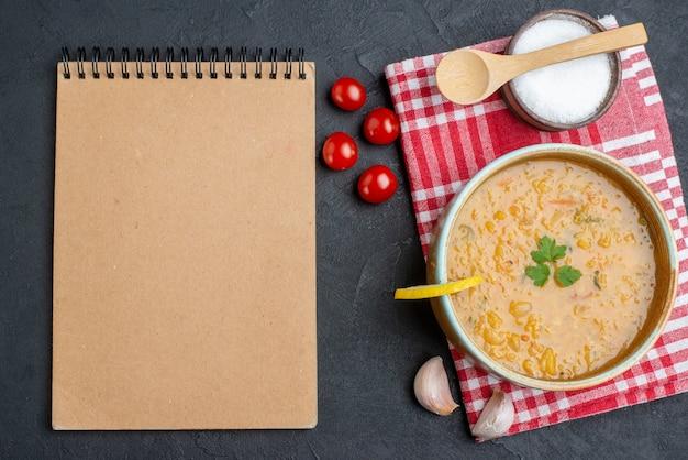 暗い表面にトマトと塩が入った上面図のおいしいレンズ豆のスープ