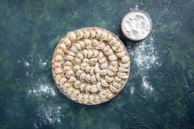 Vista dall'alto gustosi gnocchi su uno sfondo blu scuro pasta colore cibo pasto calorico cibo piatto carne