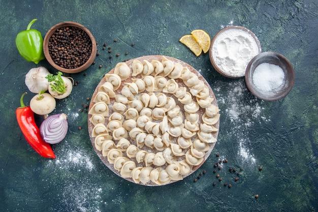 Vista dall'alto gustosi gnocchi con farina su sfondo grigio scuro pasta colore cibo pasto cibo piatto carne calorie
