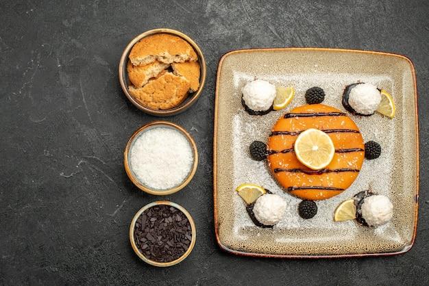 Vista dall'alto gustosa piccola torta con caramelle al cocco su superficie scura torta dessert torta biscotto tè caramelle
