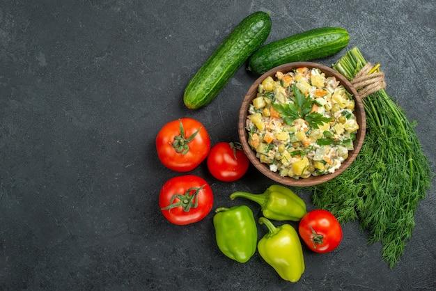 Вид сверху вкусный салат майонез со свежими овощами и зеленью на сером