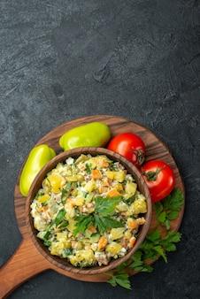 グレーに新鮮な野菜と緑を添えたトップビューのおいしいマヨネーズサラダ