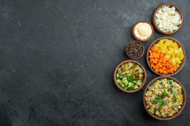 Вид сверху вкусный салат майонез с нарезанными свежими овощами на черном