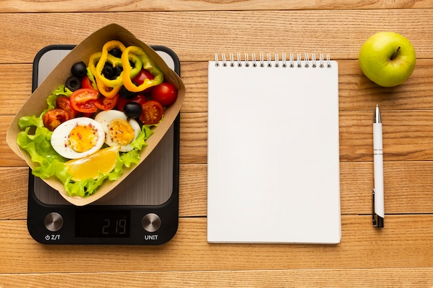Top view tasty meal composition with empty notebook
