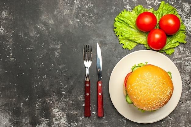 Vista dall'alto gustoso hamburger di carne con verdure su panino panino pavimento scuro fast-food