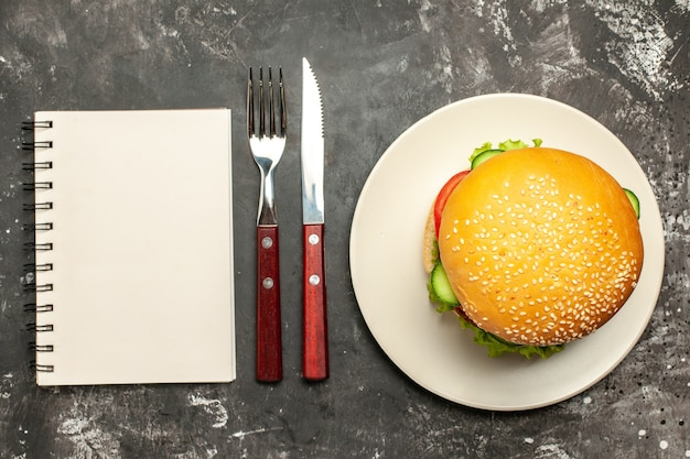 Top view tasty meat burger with vegetables on the dark surface bun sandwich fast-food