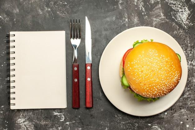 暗い表面のパンサンドイッチファーストフードに野菜を添えたトップビューのおいしいミートバーガー
