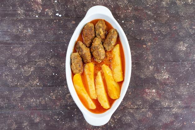 Вид сверху вкусные мясные котлеты, приготовленные вместе с картофелем и соусом внутри тарелки на коричневом фоне, блюдо из мяса и картофеля, ужин