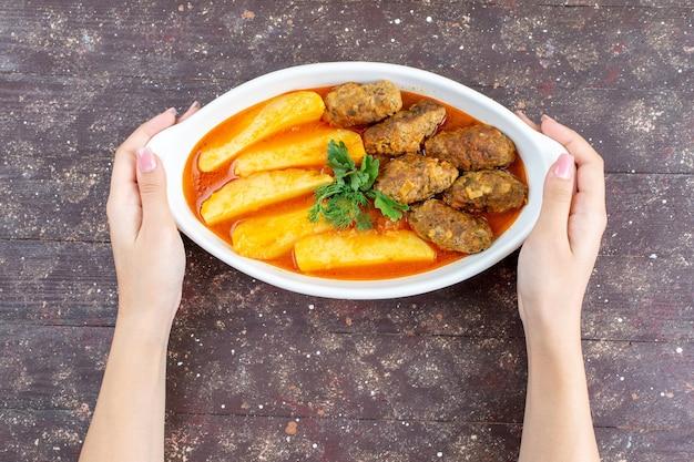 Вид сверху вкусные мясные котлеты, приготовленные вместе с картофелем и соусом внутри тарелки, взятой женщиной на коричневом фоне, мясо, картофельное блюдо, обед