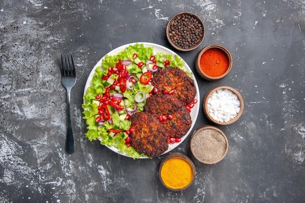 회색 배경 사진 음식 접시 고기에 신선한 샐러드와 상위 뷰 맛있는 고기 커틀릿