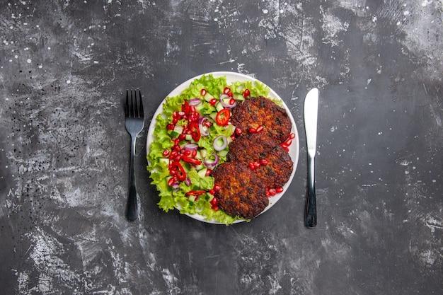 灰色の背景に新鮮なサラダを添えたトップビューのおいしい肉カツレツ写真肉料理