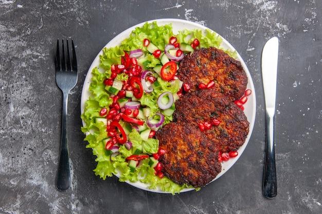 회색 배경 사진 고기 요리 음식에 신선한 샐러드와 상위 뷰 맛있는 고기 커틀릿