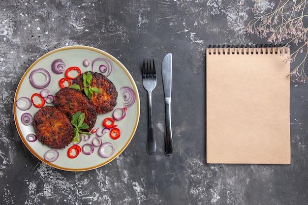 灰色の机の食事料理の写真にオニオンリングが付いた上面図のおいしい肉カツレツ