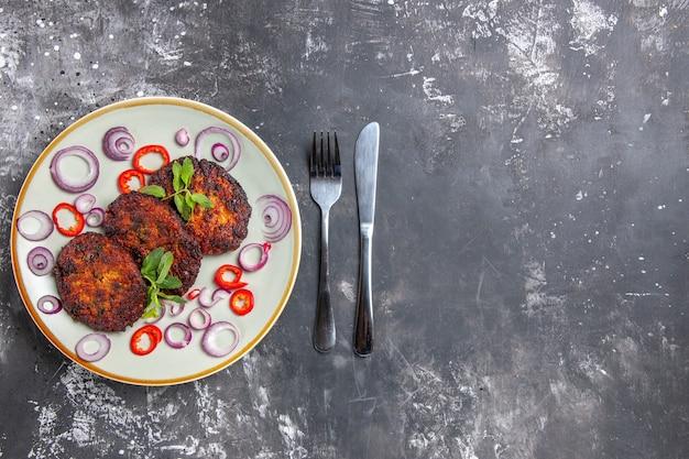 灰色の床の食事料理の写真にオニオンリングが付いた上面図のおいしい肉カツレツ
