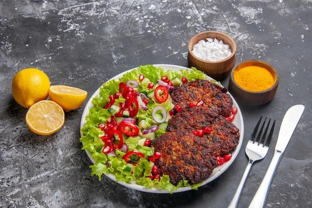 회색 배경 사진 음식 접시에 샐러드와 조미료와 상위 뷰 맛있는 고기 커틀릿
