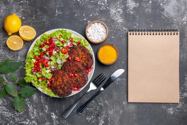 Вид сверху вкусные мясные котлеты с салатом и приправами на сером полу фото блюдо
