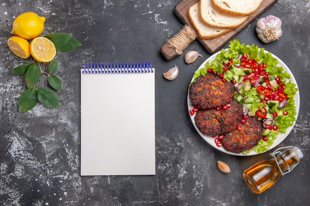 Top view tasty meat cutlets with salad and bread on a grey background dish photo food meal
