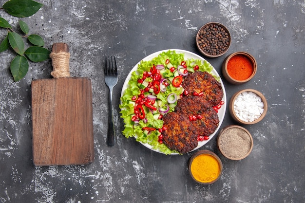 Top view tasty meat cutlets with salad and seasonings on grey background photo food dish meat