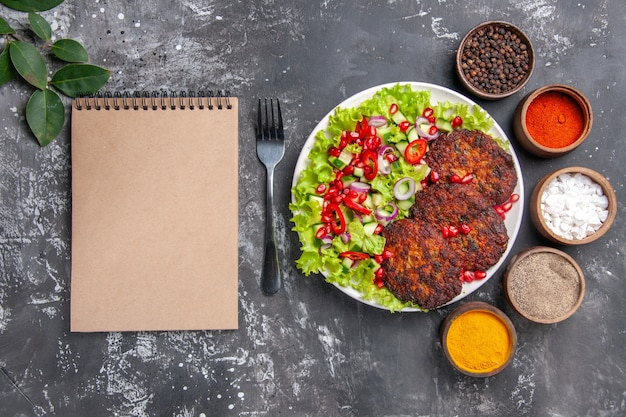 Top view tasty meat cutlets with salad and seasonings on grey background photo food dish