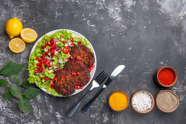Top view tasty meat cutlets with salad and seasonings on grey background photo food meal