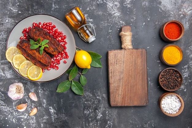 Vista dall'alto gustose cotolette di carne con condimenti sul piatto di cibo pasto sfondo grigio