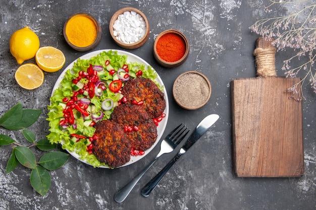 회색 배경 사진 음식 접시에 조미료와 상위 뷰 맛있는 고기 커틀릿