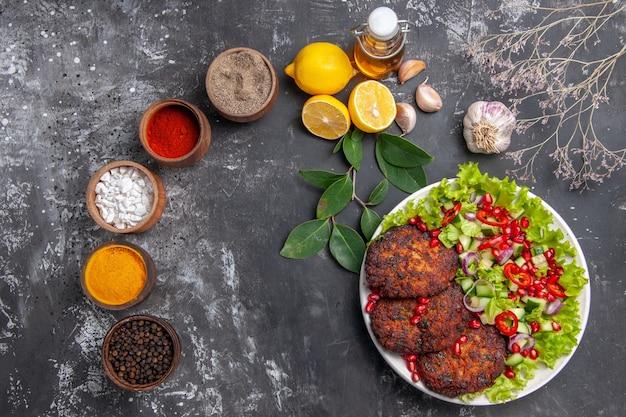灰色の背景に野菜サラダとトップビューのおいしい肉カツレツ写真フードミール