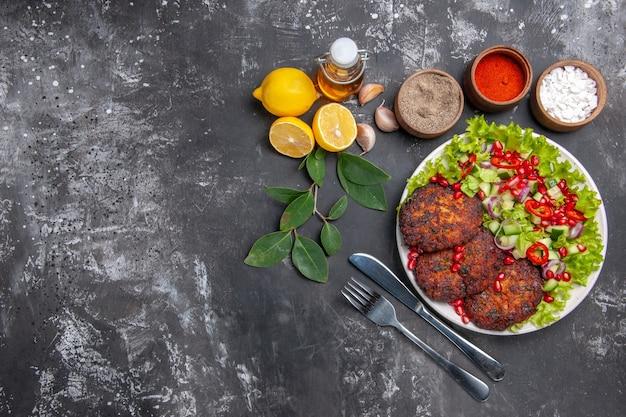 Вид сверху вкусные мясные котлеты с овощным салатом на сером столе фото еда блюдо