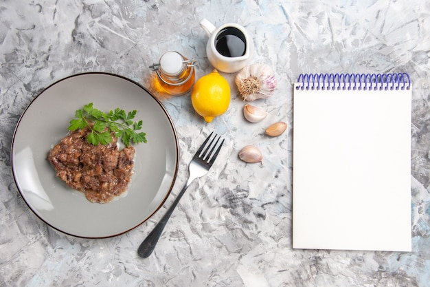 白いテーブルの上のソースと緑のおいしい肉料理の上面図夕食肉料理の食事