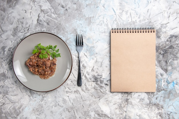 上面図白いテーブルの肉料理の夕食の食事にソースと緑のおいしい肉料理
