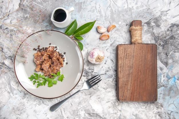 白いテーブルの上のソースのおいしい肉料理の上面図