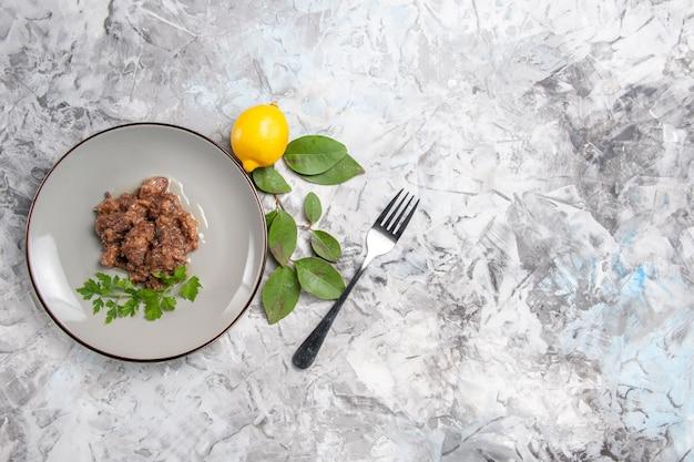 平面図ライトホワイトのテーブルディナーディッシュミールミートにソースがかかったおいしい肉料理