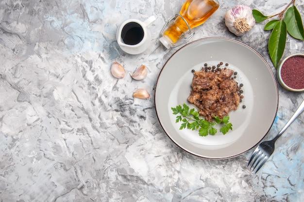 ライトホワイトのテーブルディナーミールミートディッシュにソースをかけたトップビューのおいしいミートディッシュ