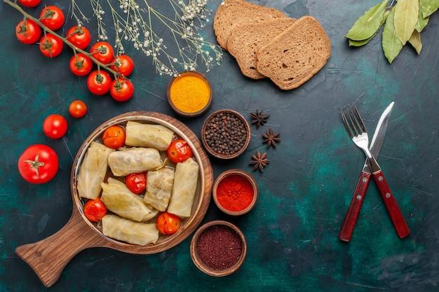 진한 파란색 책상에 빵과 신선한 토마토가 들어간 양배추 내부의 맛있는 고기 식사