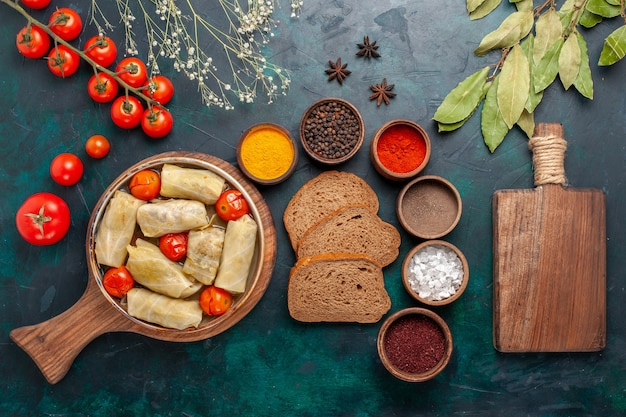 Вид сверху вкусной мясной муки, завернутой в капусту с хлебом и свежими помидорами на темно-синем столе